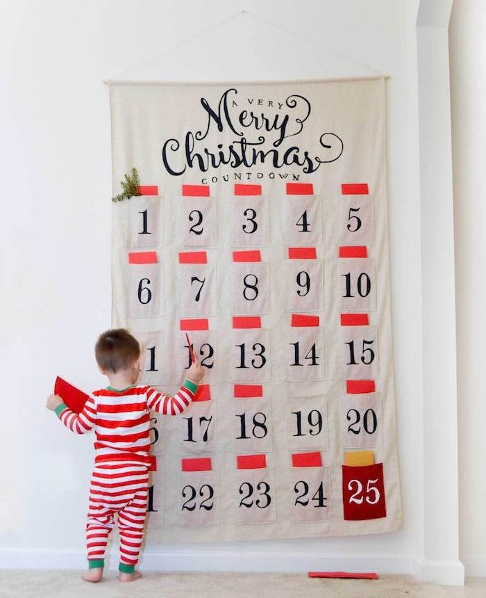 calendrier de l'avent original en toile avec des pochettes à insérer des cartes surprise et une inscription joyeux noel écrite dessus, decoration murale de noel