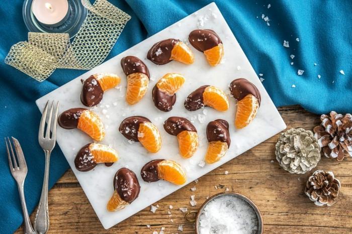 joli apéritif de fruits et de chocolat, morceaux de mandarines trempés dans du chocolat, plat de service blanc, bougie allumée, pommes de pin