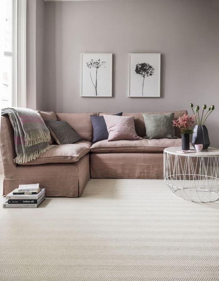 salon rose poudré avec un canapé moelleux élégant de la même tonalité que les murs, surmonté de deux cadres photos à motifs fleuris poétiques