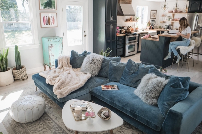 un grand canapé cosy en velours couleur bleu canard qui trône au centre d'un salon bohème chic ouvert sur la cuisine