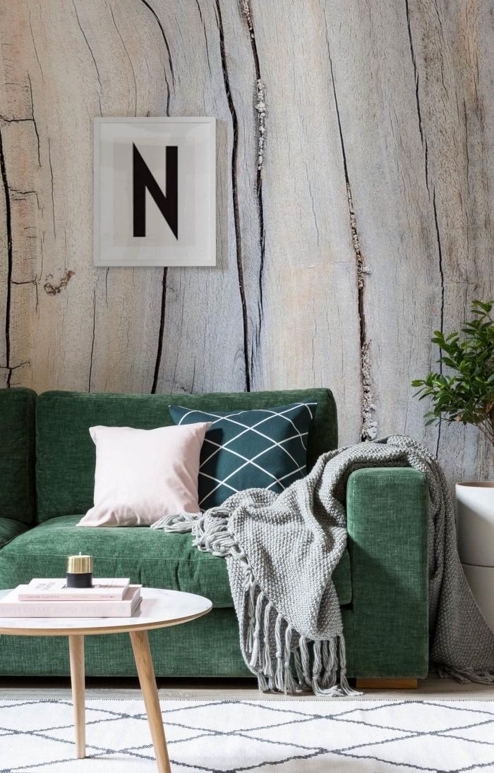 canapé cosy vert accessoirisé avec des coussins unis ou graphiques en vert et rose, posé contre un mur recouvert de papier peint trompe-l'oeil effet bois
