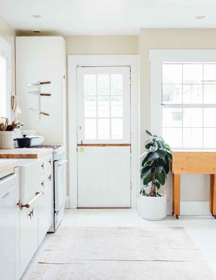 cuisine blanche élégante avec façade cuisine blanche, tapis oriental usé, plan de travail bois et caoutchouc plante en pot