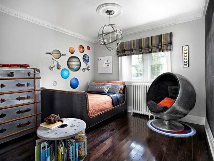 sol en bois foncé, chaise cocon grise, étagère grandes valises vintage, lit original, planète au mur, chandelier industriel