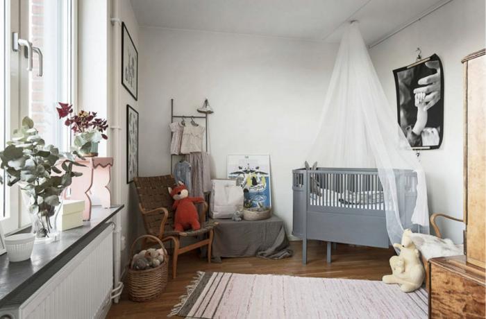 plusieurs plantes vertes, tapis vintage blanc, sol foncé, lit bébé, photo artistique au mur, chaise vintage