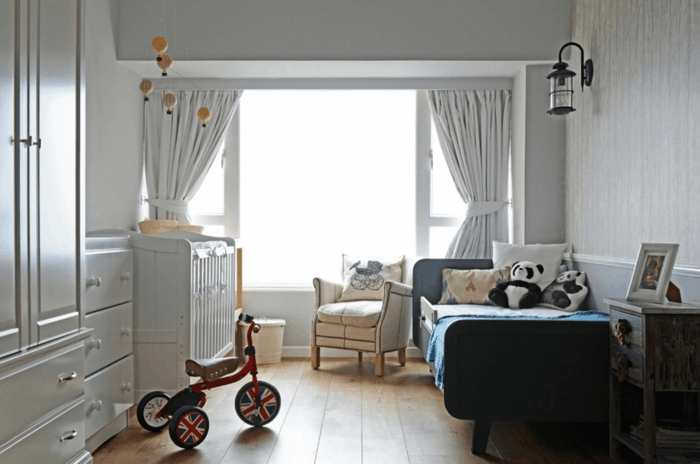 rideaux en gris clair, vélo à trois roues, lit enfant 2 ans, sol en planches, fauteuil crème, lanterne murale