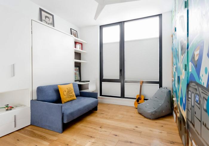 petite chambre enfant, sofa bleu, coussin bleu, étagère blanche, guitare, sol en planches