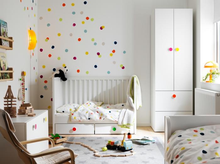 jolie déco murale à pois, tapis gris, lit bébé et armoire blanche, chaise berçante, commode blanche, applique jaune