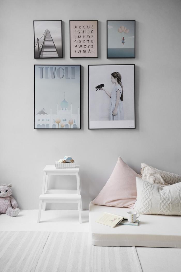 chambre enfant aménagée en style scandinave avec une galerie murale de tableaux d'art encadré, poster photo fille tenant un oiseau dans sa main