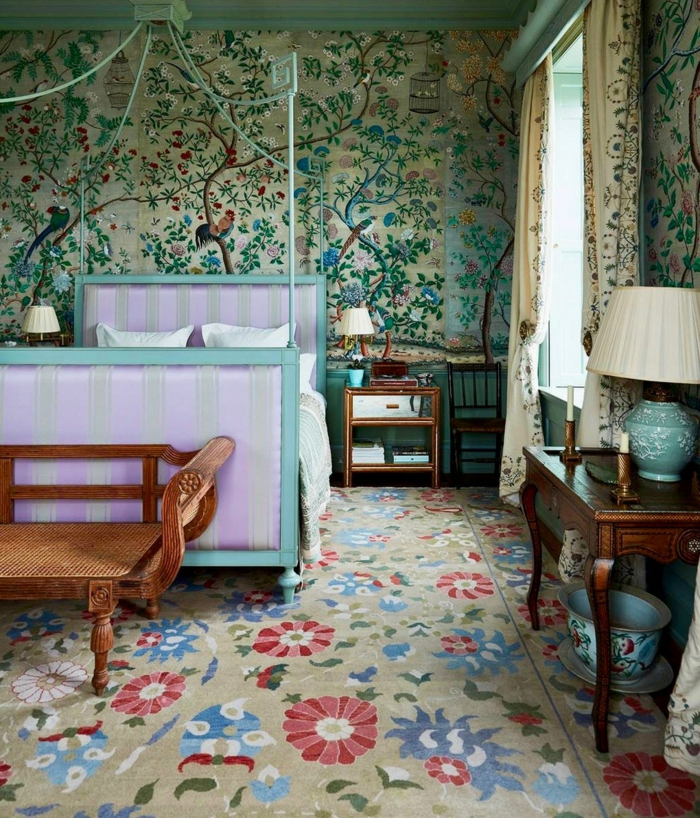 tapis motifs floraux, banquette en bois ancienne, papier peint chinoiserie, lit lilas, lampe de table, rideaux traditionnels, chevet bois et blanc