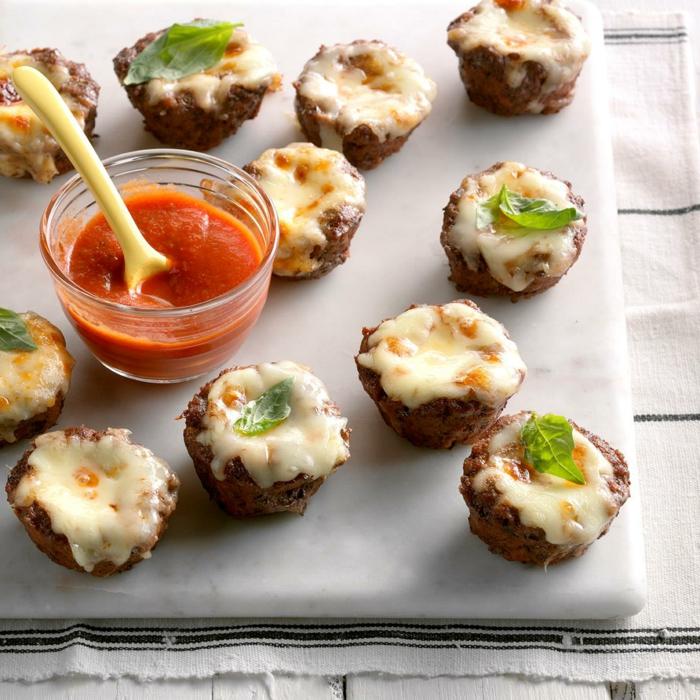 bouchées salées de noel, champignons au fromage mozzarella, épices, petite assiette pleine de sauce à la tomate