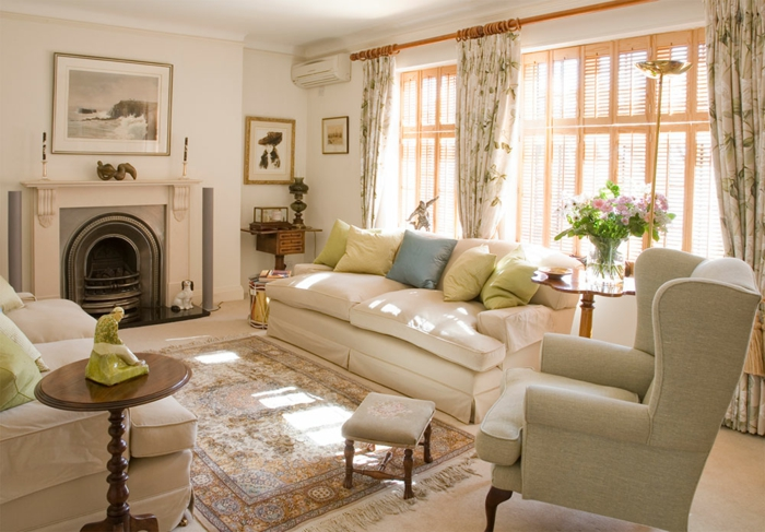 salon clair et lumineux, sofas blancs, tapis persan, grand fauteuil gris, cheminée murale blanche, rideaux floraux