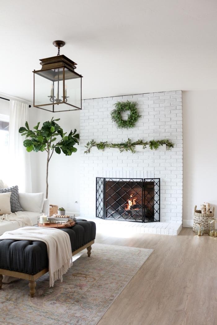 déco salon cocooning avec cheminée à manteau habillée de briques blanches qui occupe une place centrale et un repose-pied table basse accessoirisé d'un plateau déco