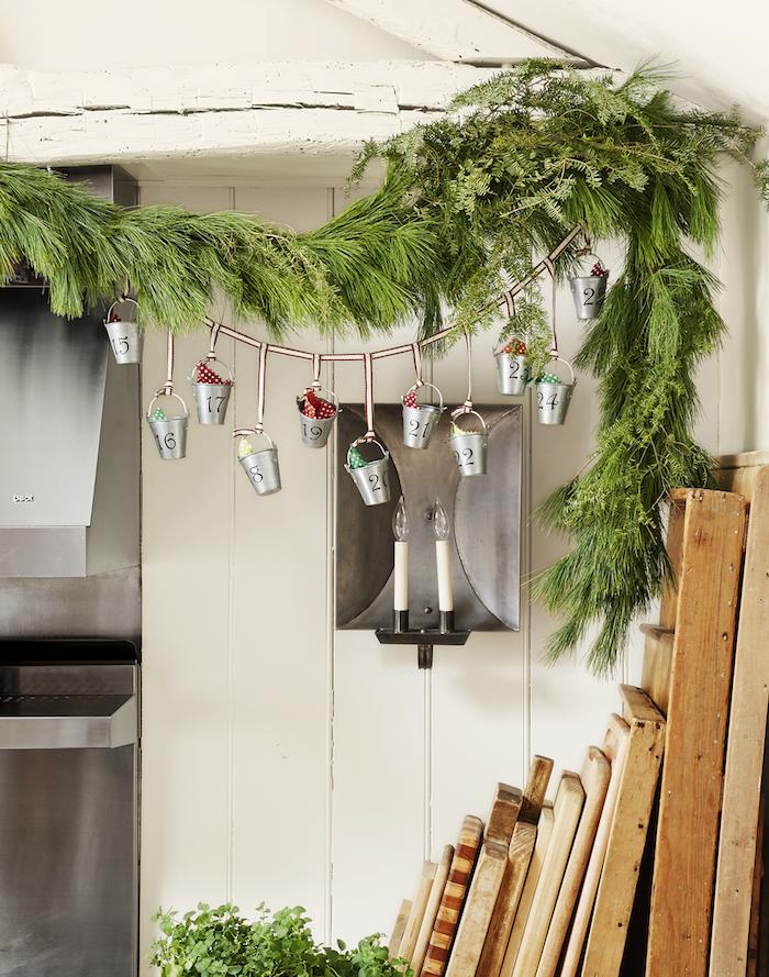calendrier de l avent en mini seaux de l avent avec des mini seaux accrochés sur un fil avec décoration de branche verte de pin