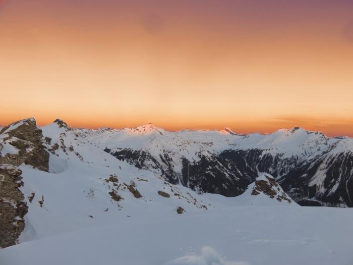 incroyable photo du coucher du soleil dans les montagnes, paysage de neige avec ciel orange et sommets enneigés