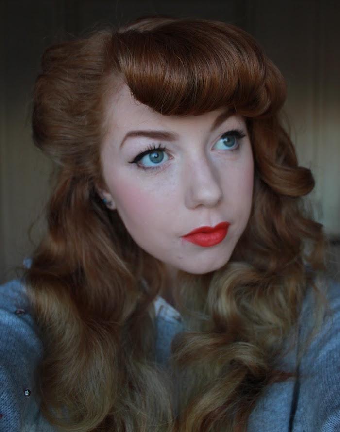 femme rousse teint pale avec maquillage années 50 lipstick et rose à joues et coiffure de pin up avec frange enroulée et boucles victory rolls