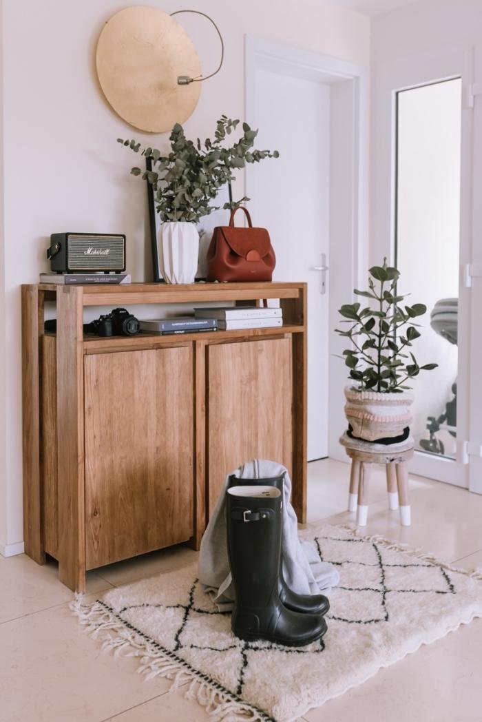 tapis cocooning frangé posé devant un meuble du salon en bois, accents naturels verts et déco vintage pour une ambiance scandinave dans le salon