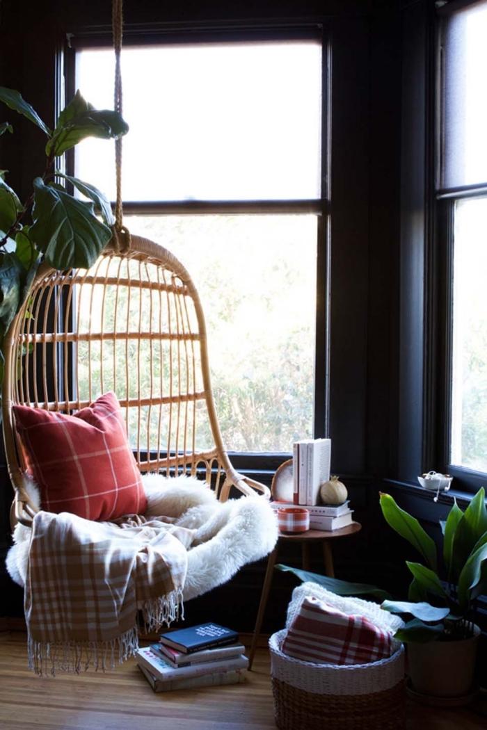 image cocooning d'un coin de lecture cosy avec balançoire d'intérieur en rotin pimpée d'une peau de mouton, d'un plaid et d'un coussin à carreaux, suspendue près de la fenêtre du salon