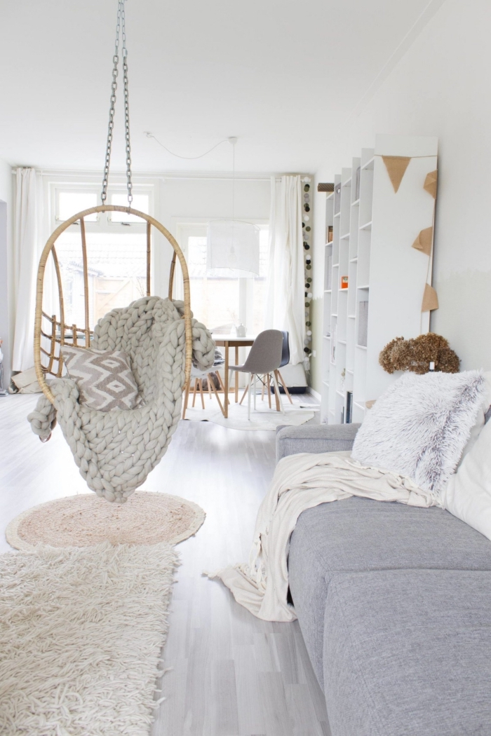 un tapis cocooning posé en dessous d'un fauteuil à suspendre cosy pour un petit coin de détente dans le salon scandinave