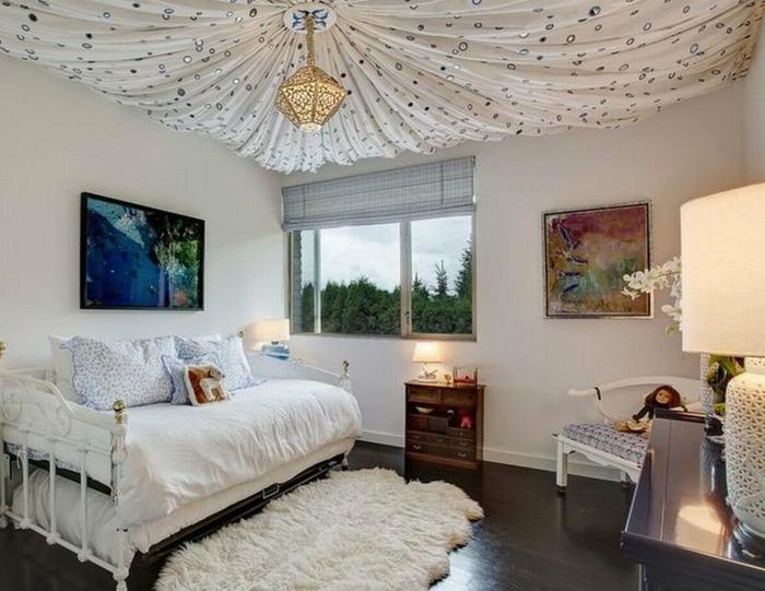 tapis fourrure blanche, lit blanc, sol en bois foncé, peintures accrochées au mur, déco plafond orientale