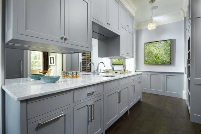 idée crédence en verre ou effet miroir, agencement cuisine avec meubles gris clair et comptoir effet marbre blanc