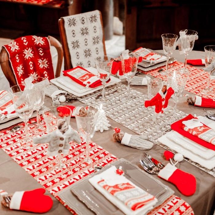 décorer une table de noel en blanc et rouge avec nappes et serviettes aux motifs flocons de neige et cerfs de noel, pliage serviette facile