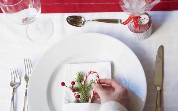 jolie décoration de table de Noel avec assiette blanche et serviette en tissu blanche, modèle pliage serviette facile pour noel