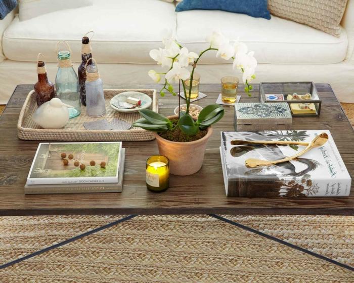 bouteilles de verre, panier en fibre naturel, pot de fleur avec orchidée, bougie allumée, grand livre monochrome, tapis de fibre authentique
