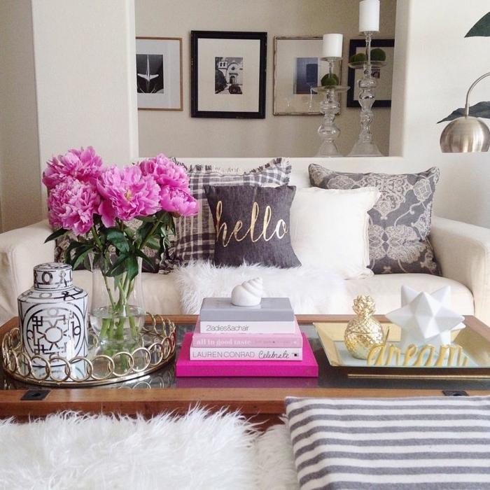salle de séjour, table basse bois, fourrures blanches, sofa blanc, grand vase avec pivoines roses, peintures encadrées, bougeoirs