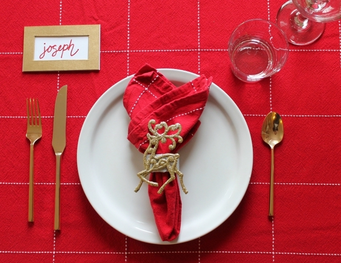 exemple de pliage serviette noel, déco table avec nappe rouge et serviette en tissu décorée de rond à serviette dorée