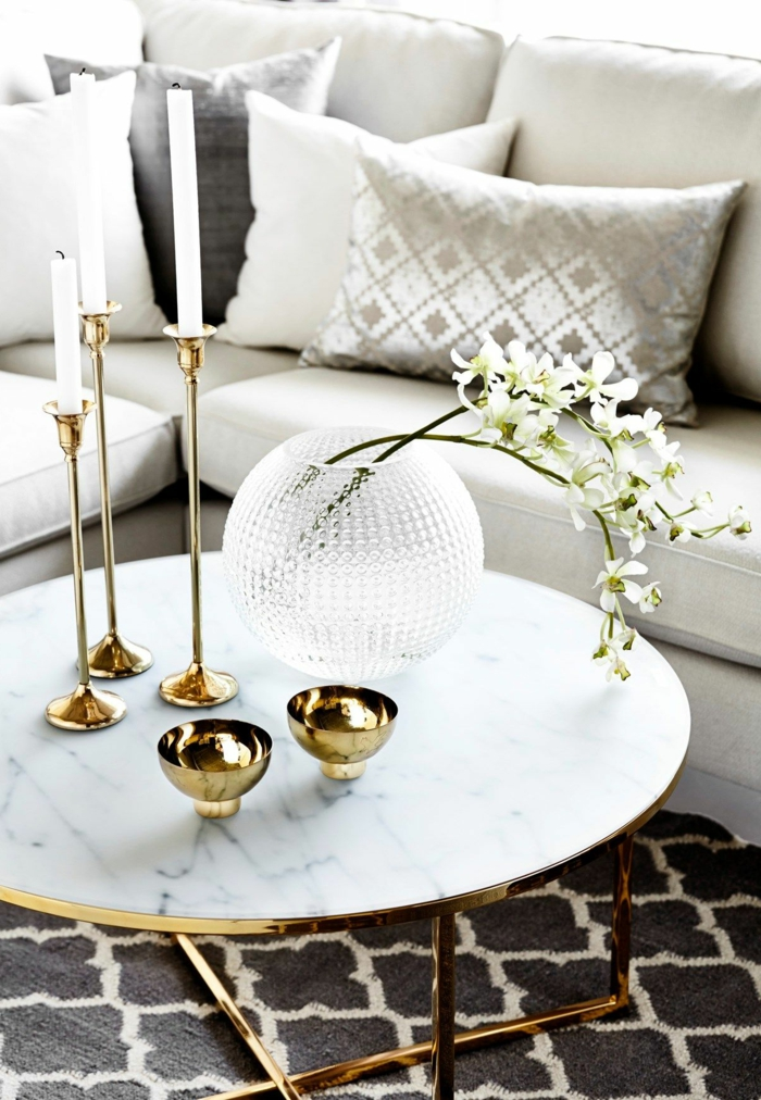 deco table basse marbre, jolis bougeoirs dorés, bougies blanches, vase boule en verre, coussins gris, deux brins de fleurs