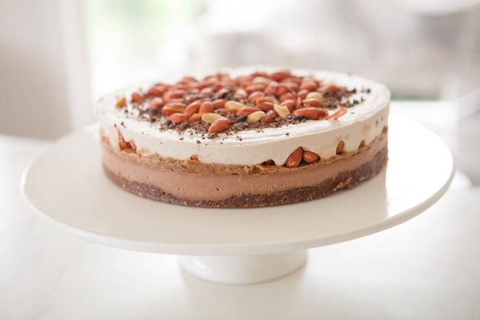 gâteau végétalien original saveur snickers et caramel, sans cuisson et sans lactose sur une vase de dattes et de noix