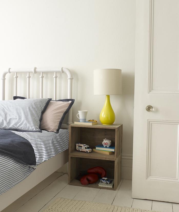 idée simple de table basse en cagettes de bois superposées avec rangement pour objets variés, lit métallique blanc, linge de lit bleu et blanc