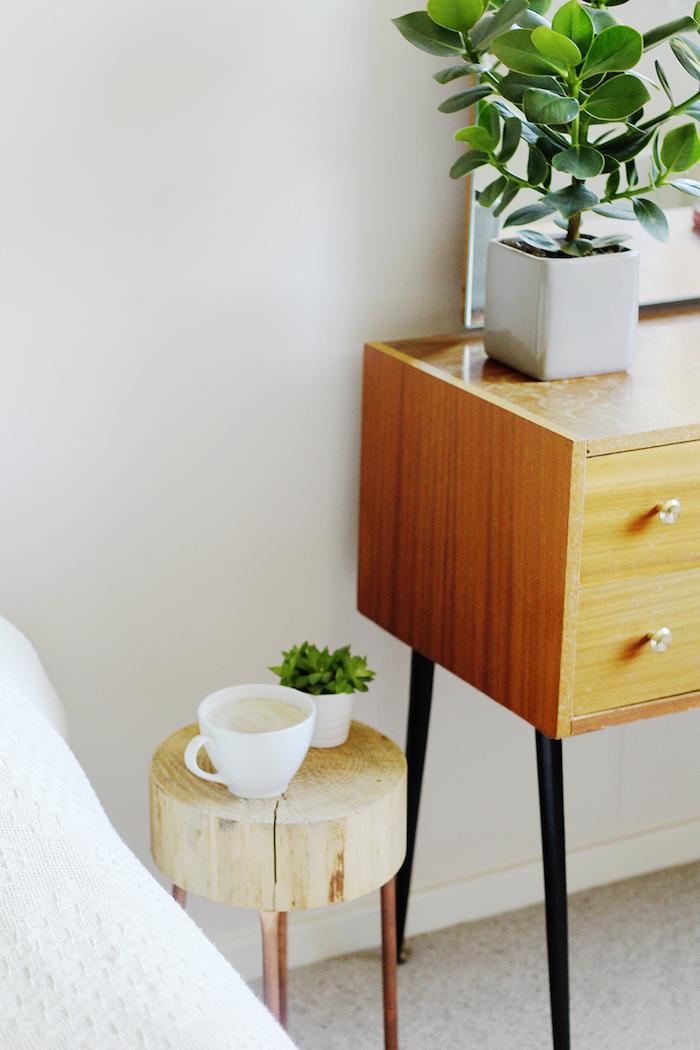 modele de table basse rondin de bois à pieds en tube de cuivre, petit pot plante verte, tasse de café et commode vintage à côté