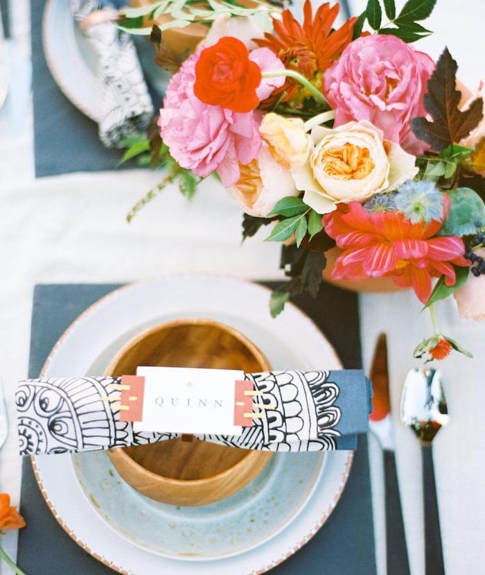 exemple de pliage de serviette en papier à motifs mandala dans assiette sur serviette carré gris, centre de table en bouquet de fleurs colorées