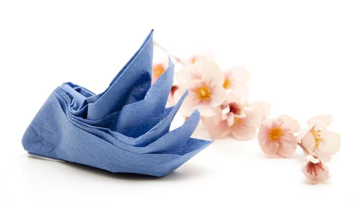 pliage de serviette en papier en forme de cygne bleu marine avec une decoration florale de brin d orchidée