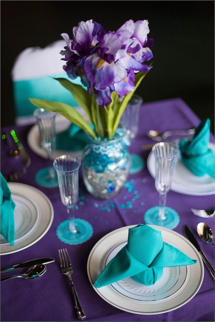 comment décorer une table de mariage en couleur violette et bleue, pliage serviette en forme de cygne bleue, nappa et fleurs violettes dans vase pailleté