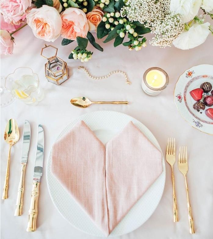 décoration de table mariage romantique, pliage serviette coeur avec deux serviettes en tissu rose, couverts dorés, composition florale mariage, bougeoirs romantiques