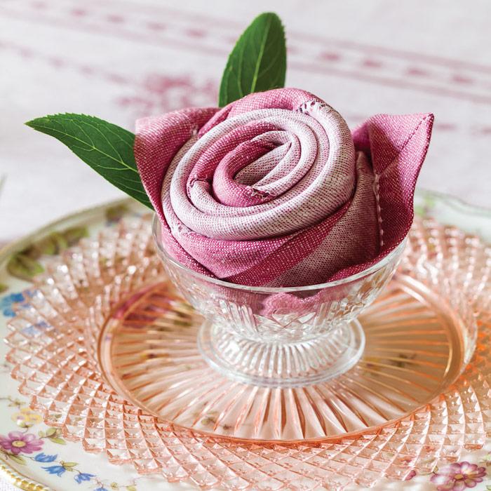 idee pour faire un pliage serviette rose original avec serviette en tissu et feuilles vertes fraiches, assiette shabby chic
