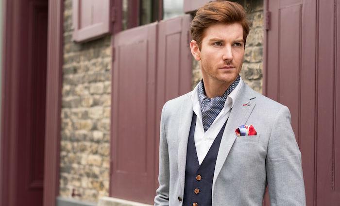 homme en costume gris clair avec gilet bleu marine et cravate lavallière ascot à pois blancs