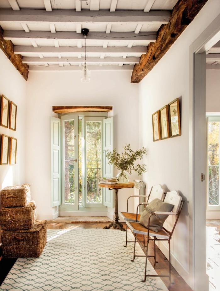 deco maison de campagne cosy, couloir en blanc et bois, poutres en bois authentique au plafond, panier rustiques superposés, tapis géométrique