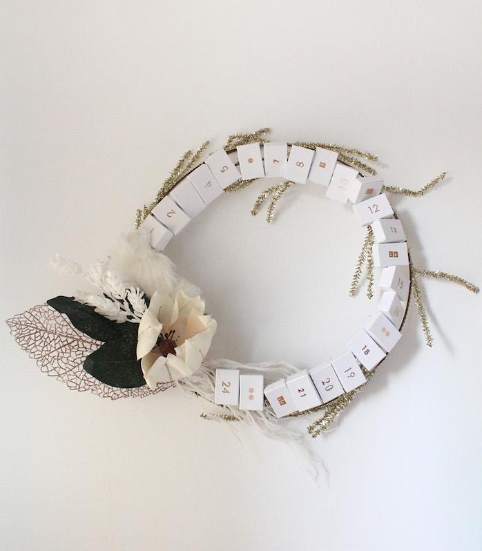 couronne de noel originale avec des boîtes d allumettes blanches et chiffres notés dessus et décoration de fleurs et branches artificielles