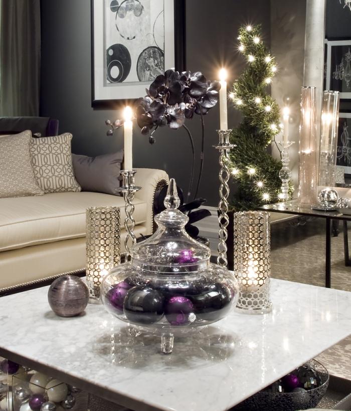 peinture murale gris anthracite, table basse verre, bougeoirs en cristal, bougeoirs métalliques, sofa crème, récipient plein de boules lilas et noires