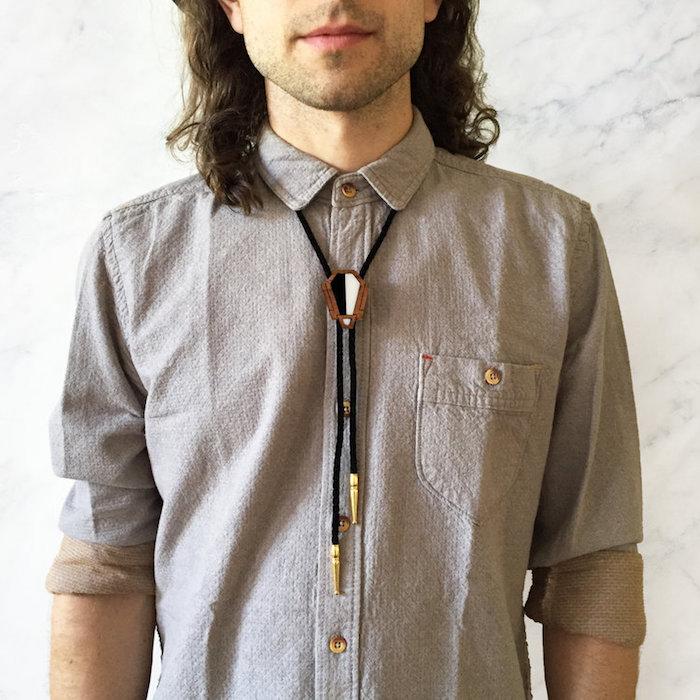homme cheveux longs avec collier bolo noir avec bijou en bois ou cravate texane sur chemise grise casual
