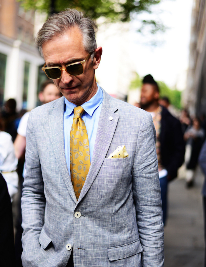 homme avec cravate en soir jaune or décorée assortie aux lunettes dorées sous costume gris clair