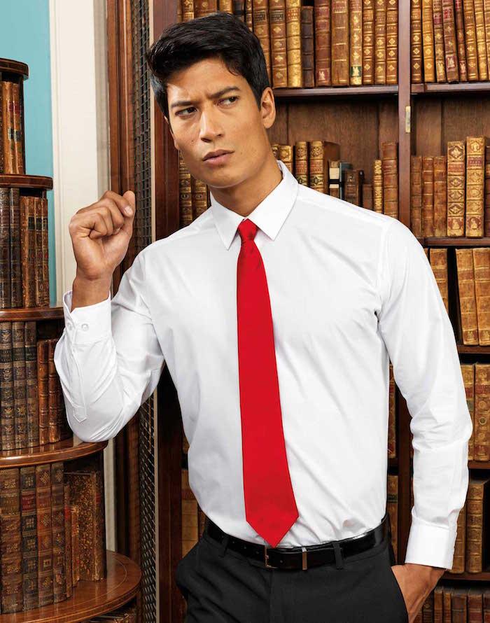 comment porter une cravate rouge vif sur chemise blanche et costume noir pour homme dans bibliothèque