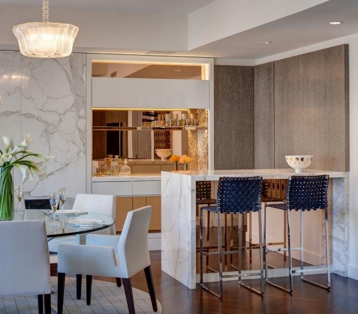 comment habiller les murs dans une cuisine sophistiquée, exemple de cuisine avec îlot en marbre et éclairage moderne