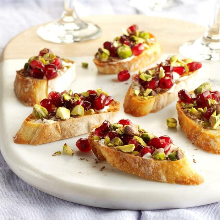 apéro dinatoire de noel, pain en tranches, pistaches et graines de grenade, plateau en bois, verres à vin