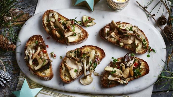 apéro dinatoire noel avec tartines, champignons tranchés, herbes fraîches, assiette blanche, pommes de pin