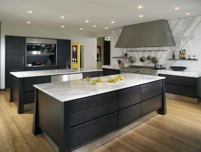 modèle de cuisine stylée en blanc et noir avec sol en bois, idée cuisine avec deux îlots, exemple agencement cuisine spacieuse
