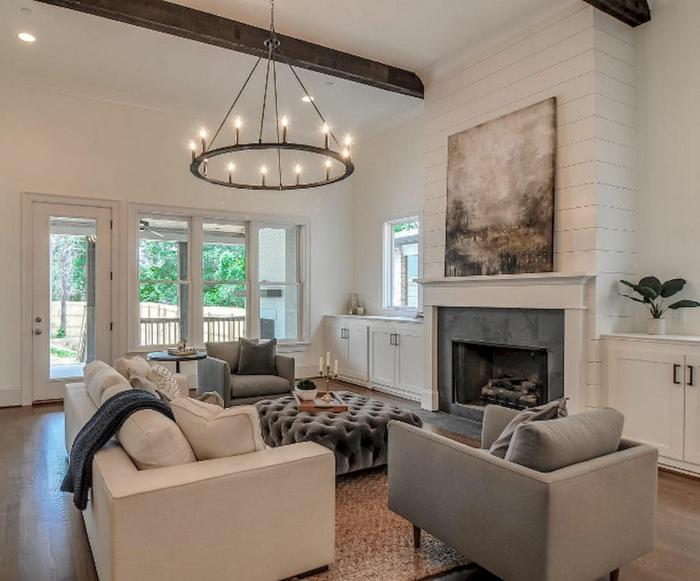 salon à decoration shabby romantique, grand chandelier noir, sofa crème, fauteuils gris épurés, cheminée, placards blancs, tapis sisal